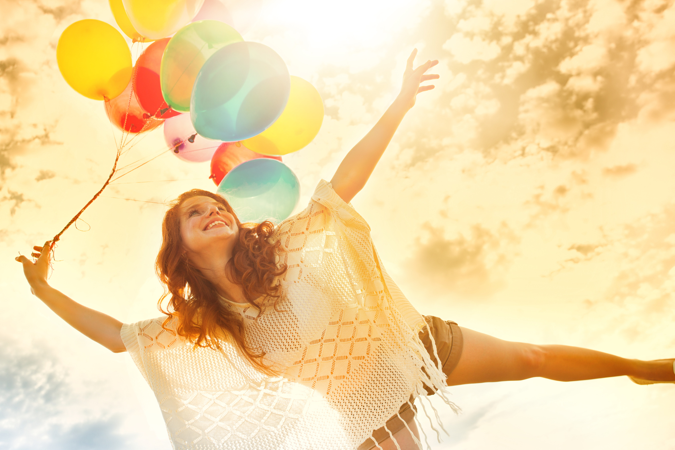 Frau mit Luftballons im Sonnenlicht